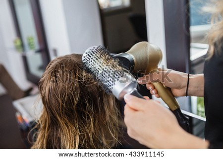 Hairdresser Styling Client's Hair In Salon - stock photo