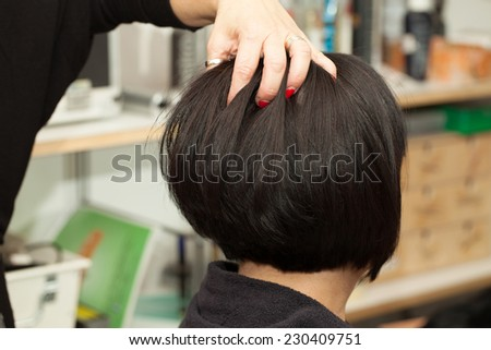Hairdresser styling the hair of client in a salon. - stock photo