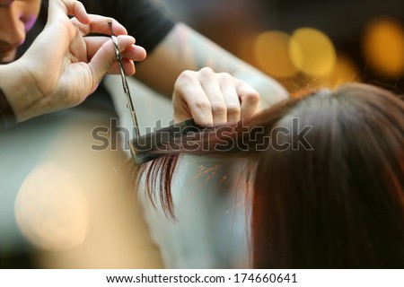 Hairdresser trimming blond hair with scissors - stock photo