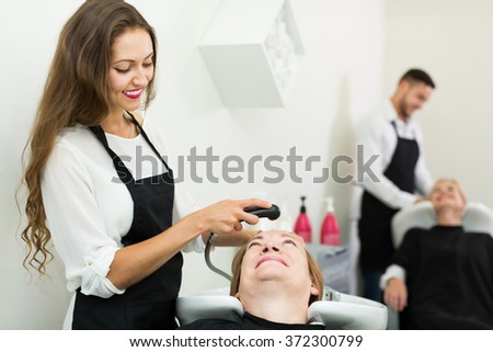 hairdresser wash head to the elderly woman in the salon - stock photo
