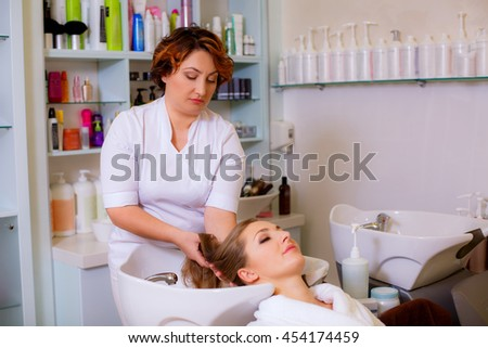 hairdresser washes head girl in a beauty salon - stock photo