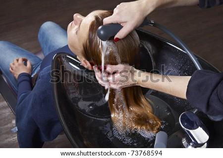 Hairdresser washing woman hair - stock photo