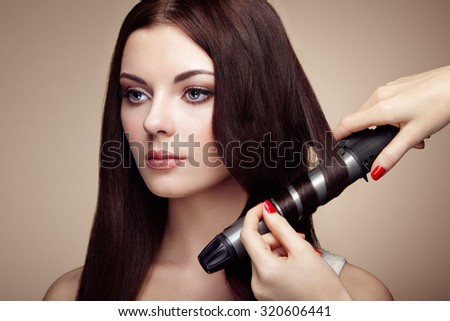 Hairdresser woman curls her hair. Portrait of young beautiful girl with luxurious hair. Fashion and beauty. Perfect make-up - stock photo