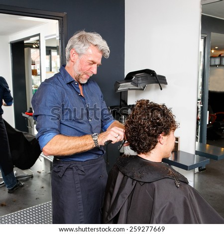 hairdresser works on the hair of a customer