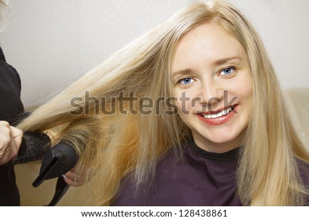 Hairdressers hands drying long blond hair with blow dryer and round brush - stock photo