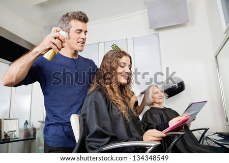 Hairdressers setting up customer's hair in beauty salon - stock photo