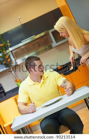haired girl puts food out of frying pan hungry guy sitting at kitchen table with a fork in my hand