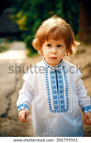Haired one year old boy plays happily in a park - stock photo