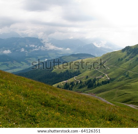 Hairpin bends on road up the grassy slopes on cloudy day in Switzerland - stock photo