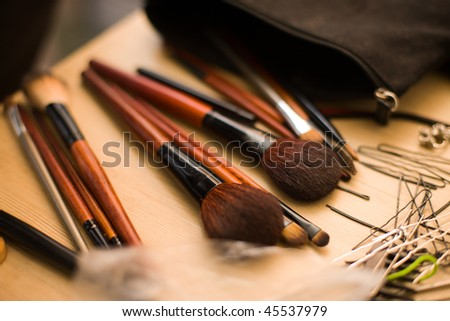 Hairpins and Brushes for makeup on table selective focus - stock photo