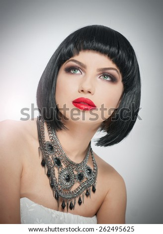 Hairstyle and Makeup - beautiful female art portrait with beautiful eyes. French style brunette, studio shot. Portrait of a attractive woman with red lips, naked shoulders and glamorous necklace - stock photo