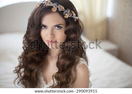 Hairstyle. Beautiful brunette bride girl with long healthy wavy hair styling posing in modern interior.