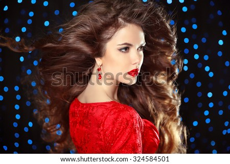 Hairstyle. Beautiful Brunette Girl. Fashion luxury earrings. Healthy Long Hair. Red lips. Beauty Model Woman. Elegant lady over holiday party lights background.