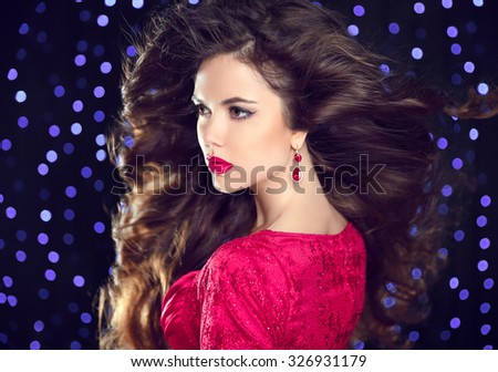 Hairstyle. Makeup. Brunette attractive woman with Fashion earring jewelry, make-up, long wavy and curly hair styles. Elegant lady posing over holiday party lights background.