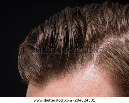 Hairstyle on male person with brown hair at closeup isolated towards black background - stock photo
