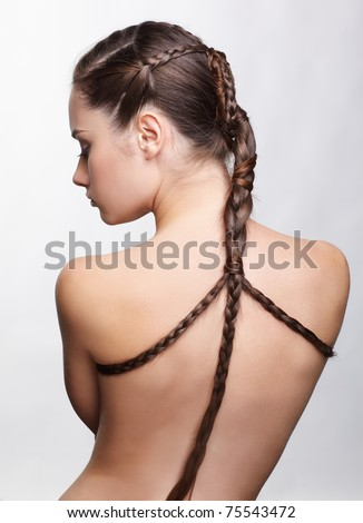hairstyle portrait of beautiful brunette girl with creative braid hairdo standing back to camera - stock photo