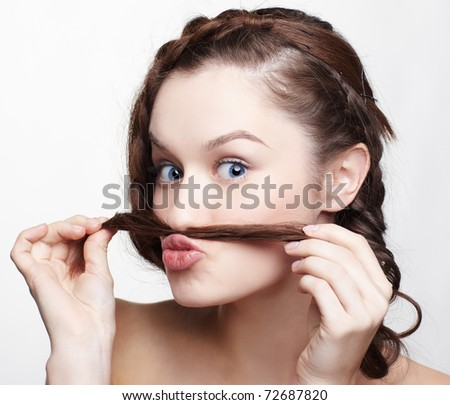 hairstyle portrait of beautiful brunette girl with creative hairdo putting braid's tail end like moustache