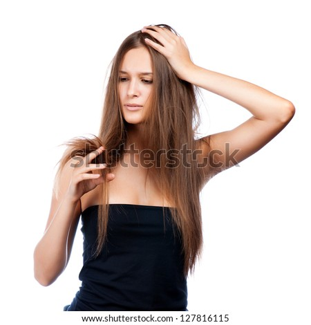 hairstyle portrait of shocked; beautiful brunette girl with creative braid hairdo looking at splitting ends - stock photo