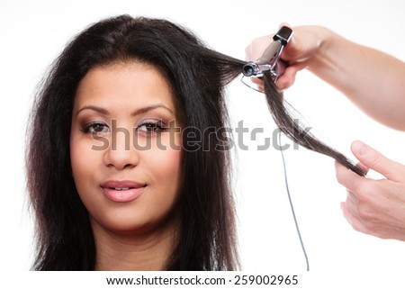 Hairstyling. attractive mixed race woman with long hair making hairstyle hairdo with electric hair curler iron on white - stock photo
