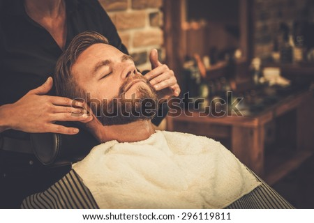 Hairstylist applying after shaving lotion in barber shop - stock photo