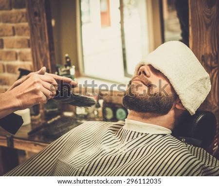 Hairstylist applying  beard powder in barber shop - stock photo