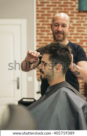 Hairstylist making men's haircut to an attractive man in the beauty salon.
