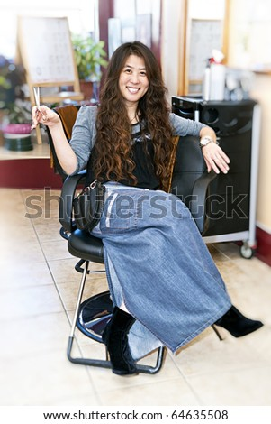 Hairstylist sitting in a chair in her hair salon - stock photo