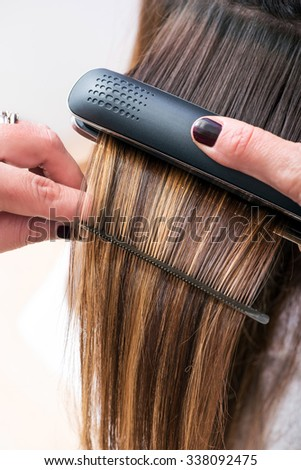 Hairstylist straightening the long brown hair of a female client using a heated hair straightener, close up view of her hands