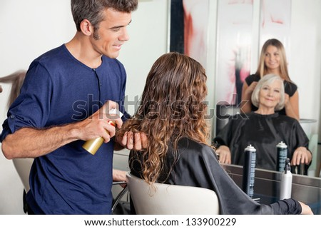 Hairstylists setting up client's hair at beauty salon - stock photo