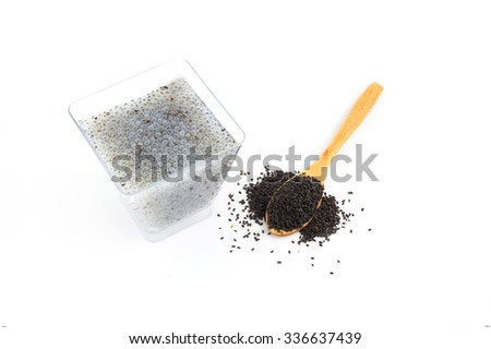 Hairy basil seeds in small glass and wooden spoon on white background.
