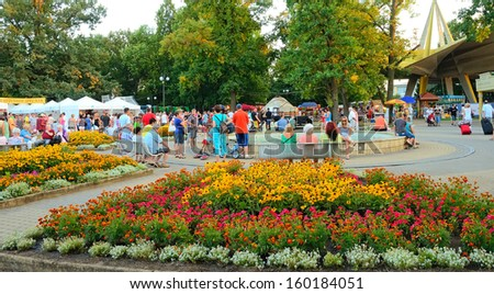 HAJDUSZOBOSZLO, HUNGARY - JULY 26: Tourists visit the center of Hajduszoboszlo, Hungary on July 26, 2013. Hajduszoboszlo is a popular spa resort in Hungary. It is located 202 km east of Budapest. - stock photo