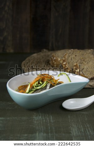 Hake in broth with carrot and zucchini on dark background - stock photo