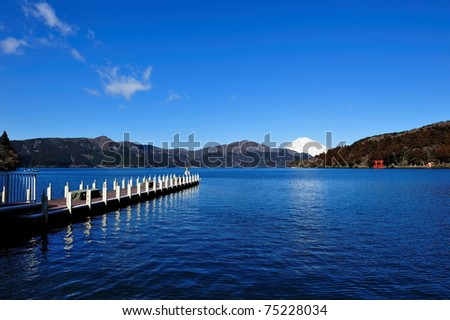 Hakone Lake and Mount Fuji in Japan, with a torii gate from Hakone's shrine at the far end shore of the lake