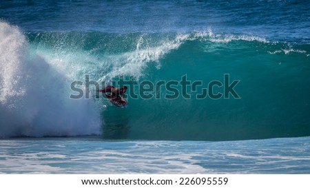 Haleiwa, HI, USA - January 17, 2013 : Bodyboarder in the tube  at Banzai Pipeline on the North Shore of Oahu - stock photo