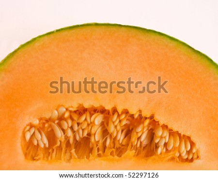 half a cantaloupe showing seeds, flesh and rind, isolated on white - stock photo