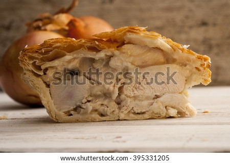 Half a chicken and onion pie on a wooden surface with bulbs of fresh onions in the background. - stock photo