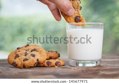 Half a chocolate chip cookie getting dunked in a glass of milk