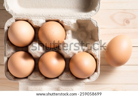 half a dozen of chicken eggs in the paper container that made from recycle paper on pine wood - stock photo