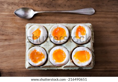 Half a dozen soft boiled eggs in a crate cardboard box. - stock photo