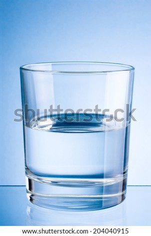 Half a glass of drinking water on blue background - stock photo
