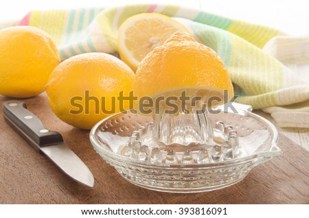 half a lemon is squeezed on a lemon squeezer - stock photo