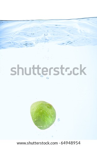 half a lime just after falling under the water surface - stock photo
