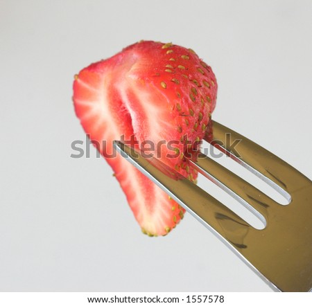 Half a strawberry and fork - stock photo