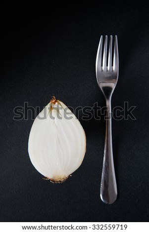 Half a yellow onion with stainless steel fork - stock photo