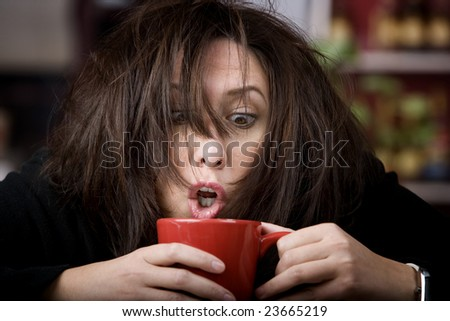 Half awake woman cradling a mug of coffee - stock photo