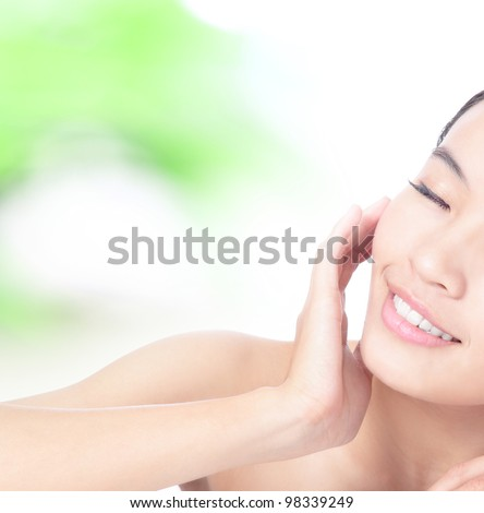 Half beautiful woman Face and hand touch face with smile on green background, model is a asian beauty - stock photo