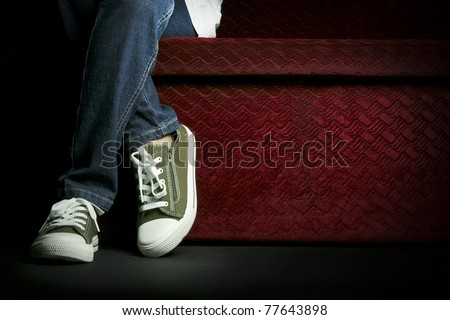 Half body of a female teenager, posing her jeans and sneakers, sitting on a red sofa. - stock photo