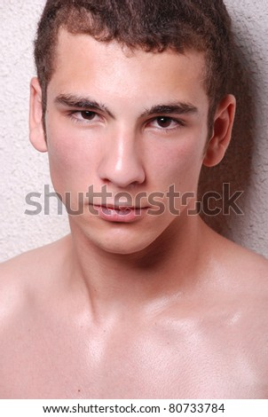 Half body portrait of bare chested young man, light background. - stock photo