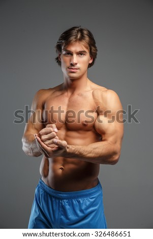 Half body portrait of muscular guy in blue shorts. - stock photo