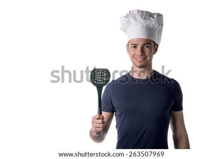 Half Body Portrait of Young Male Chef Wearing Casual Black Shirt and White Hat with Black Ladle on Hand While Looking at the Camera. Isolated on White Background. - stock photo